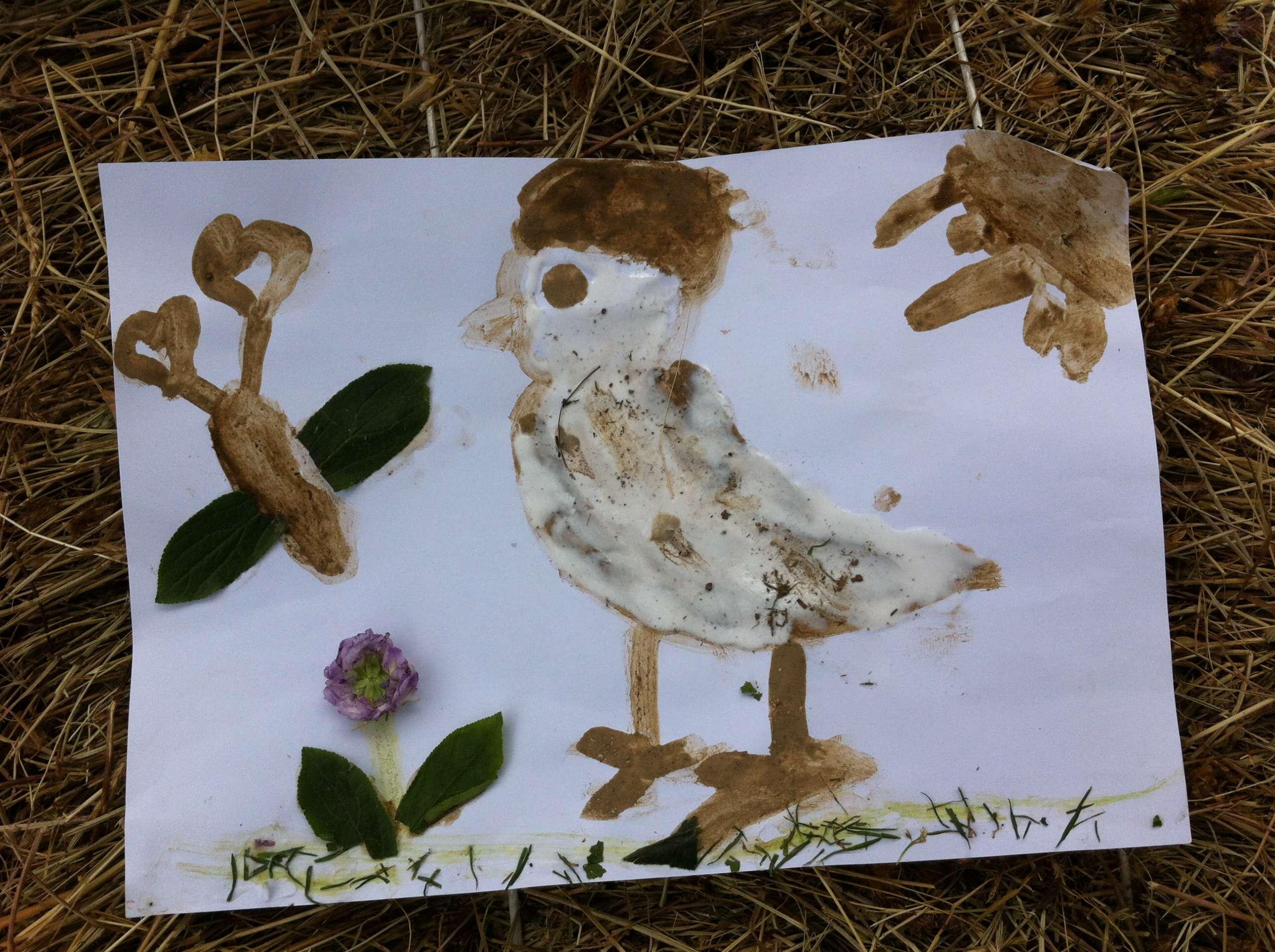disegno di uccello fatto con terra bagnata foglie erba e fiori